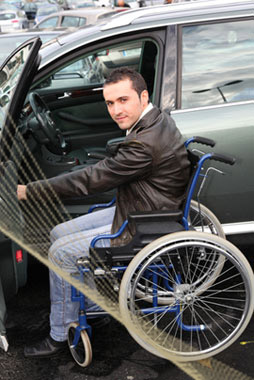 Disabled Man enters car from wheelchair
